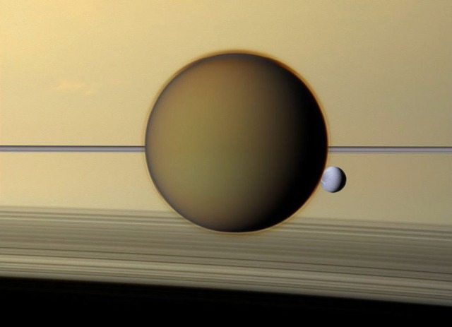 Saturn's fourth-largest moon, Dione, can be seen through the haze of the planet's largest moon, Titan, in this view of the two posing before the planet and its rings from NASA's Cassini spacecraft, in December of 2011.